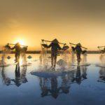 Vietnamiens travaillant dans les marais salants au couché de soleil près de Nha Trang, Vietnam