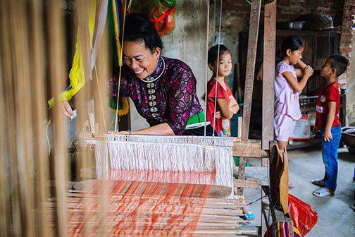 Femme Thai tissant dans sa maison à Nghia Lo, Vietnam