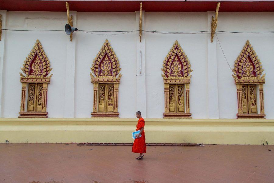 Jeune moine avec son cahier d'écolier passant devant un templs à Vientiane, Laos