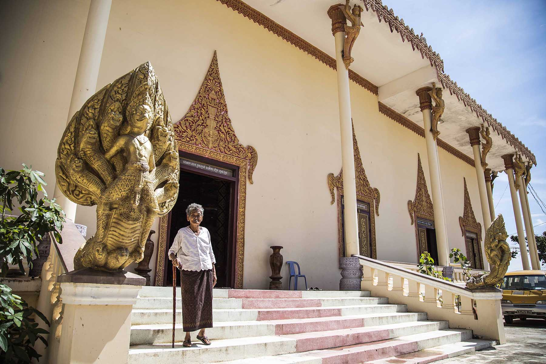 Une vieille femme devant un temple au Cambodge