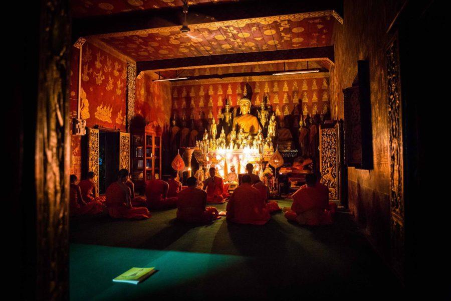 Prière des moines dans l'obscurité d'un templs de Luang Prabang