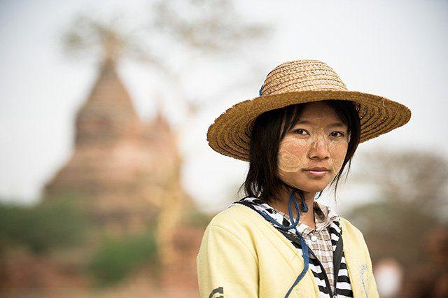 Femme arborant la peinture thanaka sur ses joues posant devant un temple de Bagan, Birmanie, Vietnam