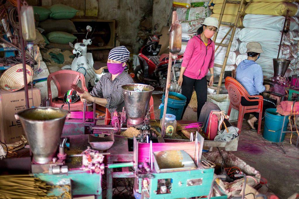 Femmes aux machines mettant l'encens sur le bambou, Vietnam