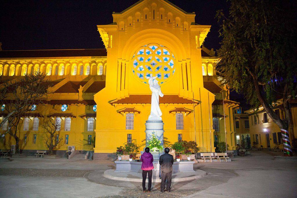 Personnes en train de prier devant une eglise de Hanoi avant Noël, Vietnam