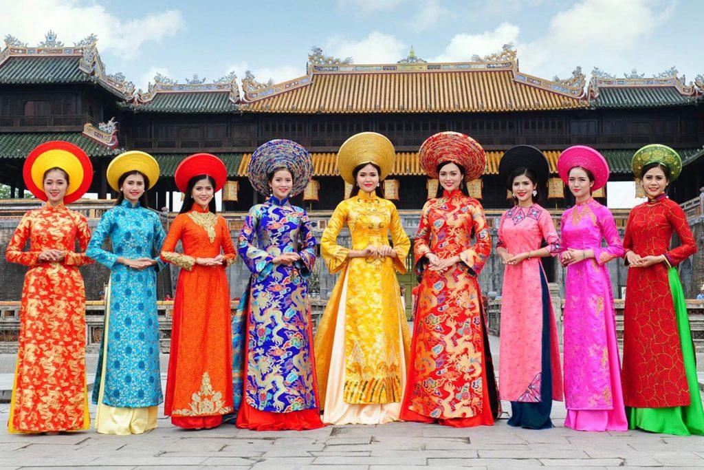 Femmes en Ao Dai traditionnel posant devant la Citadelle, Hue, Vietnam