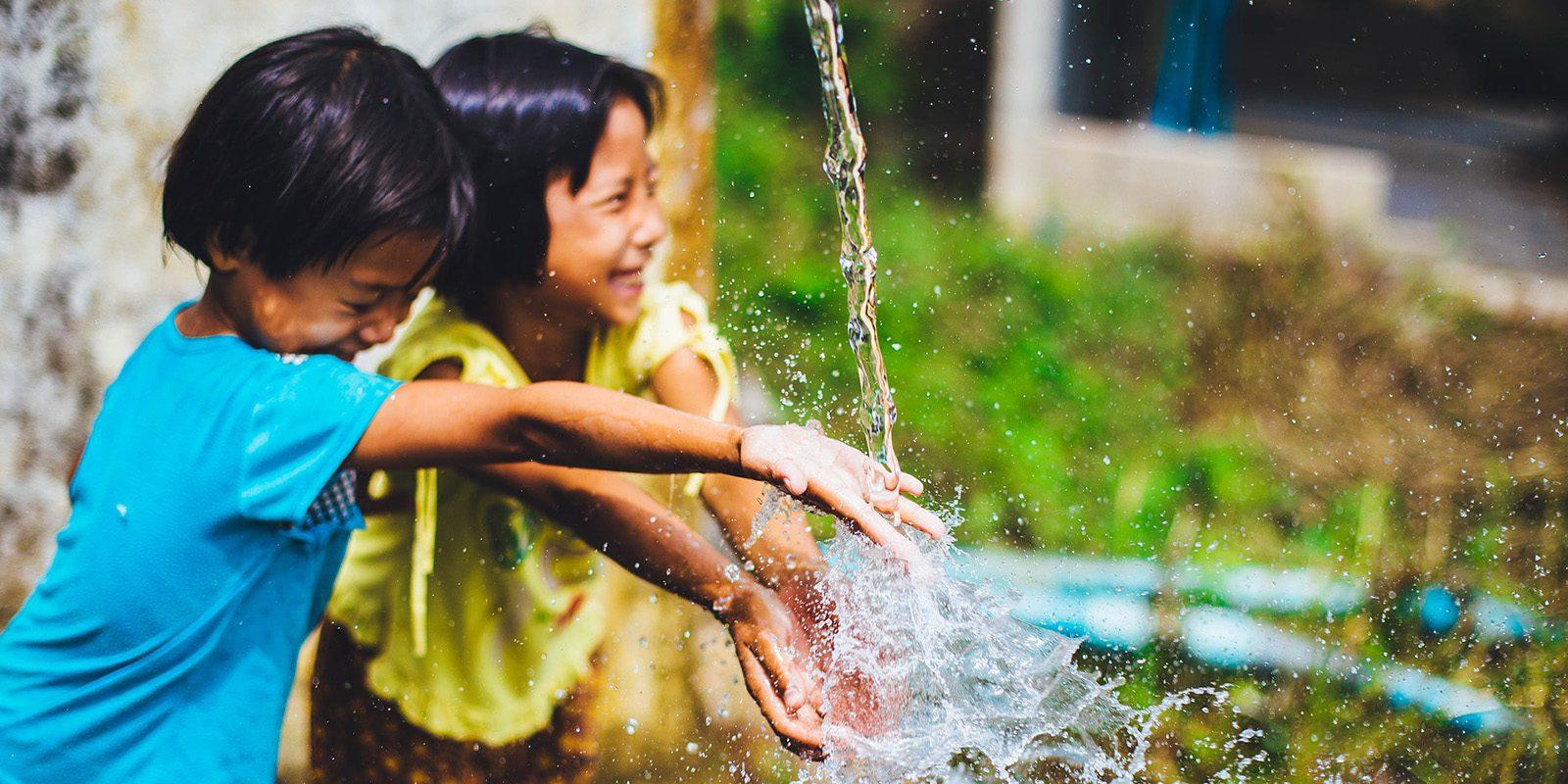 Enfants jouant avec une fontaine à eau, Vietnam