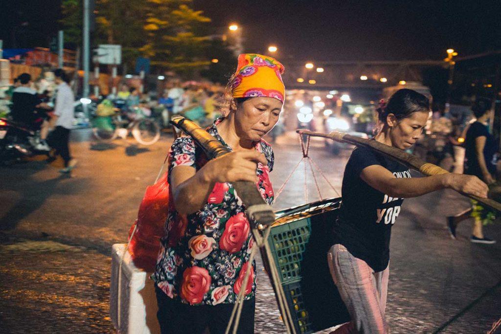 Vendeuses ambulantes sortant du marché Long Bien, Hanoi, Vietnam