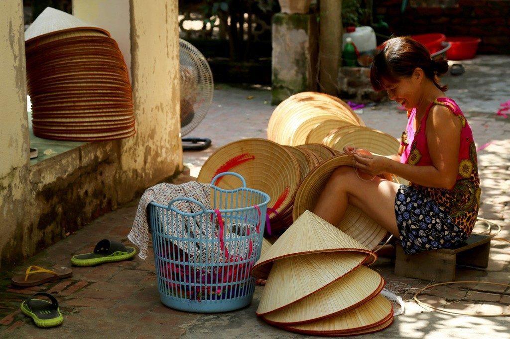 Femme en train de confectionner des chapeaux coniques au village de Chuong