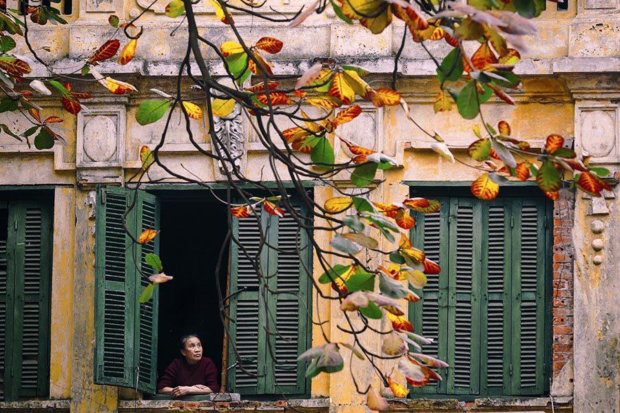 Habitant du vieux quartier de Hanoi à sa fenêtre