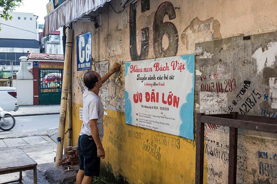 Résident prenant soin des affiches de publicité en bas de son immeuble, Hanoi